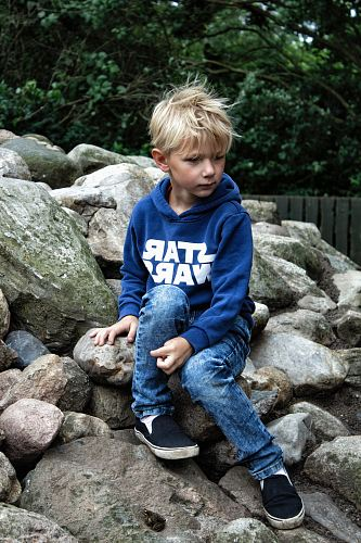 boy seating on rock fragments