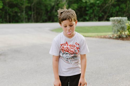 photo boy standing on gray concrete road while tongue out free for commercial use images