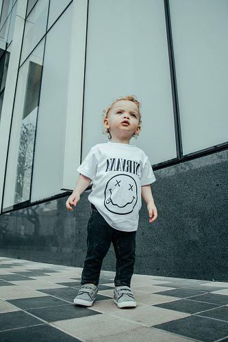 child in Nirvana shirt standing near building