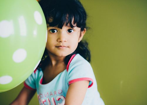 girl holding green balloon
