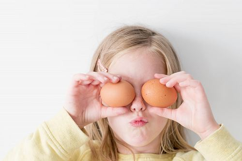 photo girl holding two eggs while putting it on her eyes free for commercial use images