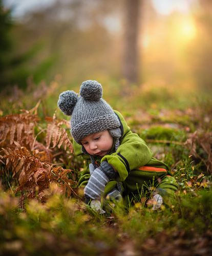 selective focus photo of baby on green grass field