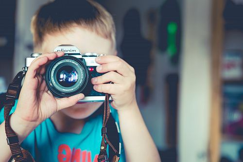 selective focus photography of boy holding gray Minolta bridge camera