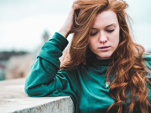 photo selective focus photography of woman wearing green long-sleeved top leaning on wall free for commercial use images