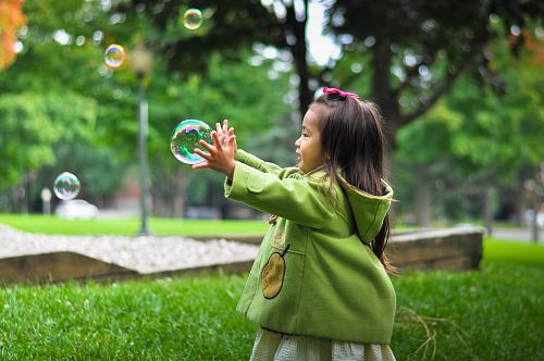 photo selective photo of a girl holding bubbles free for commercial use images