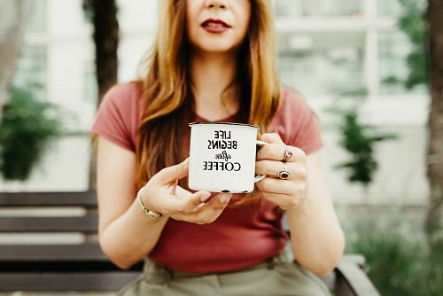 photo woman holding mug during daytime free for commercial use images