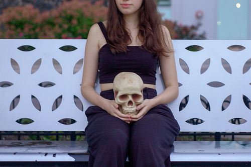 photo woman holding skull sitting on bench free for commercial use images