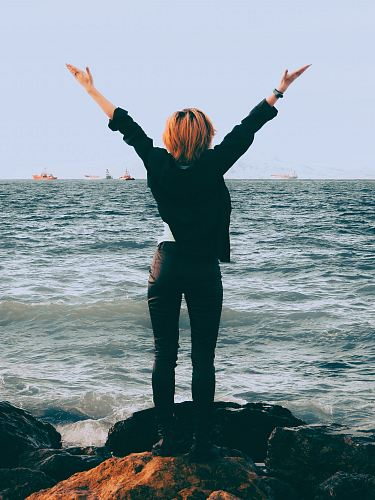 woman standing on shore near sea