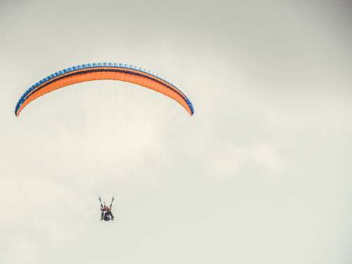 gliding orange and blue parachute leisure activities