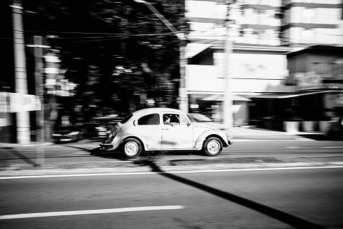 car grayscale photo of white Volkswagen Beetle car running on gray road transportation