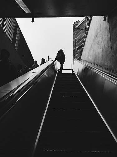 banister silhouette of person standing beside escalator during daytime handrail