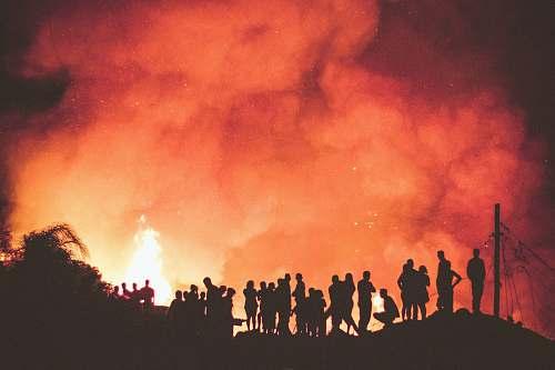 fire people near bonfire during night orange