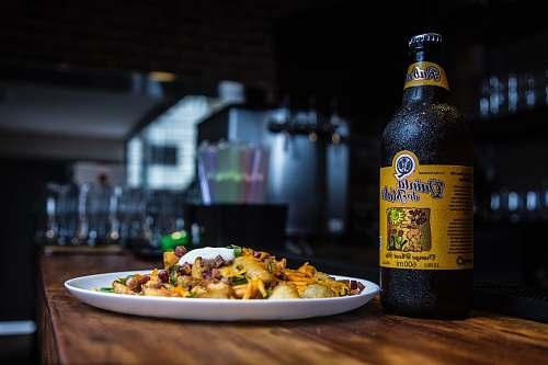 beer Quinta bottle beside cook food on brown wooden table são paulo