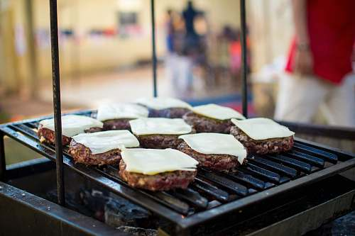 food selective focus photography of meat patty with cheese on grill bbq