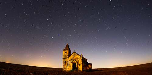 night worm's eye view photography of cathedral under gray skies filled of stars outdoors