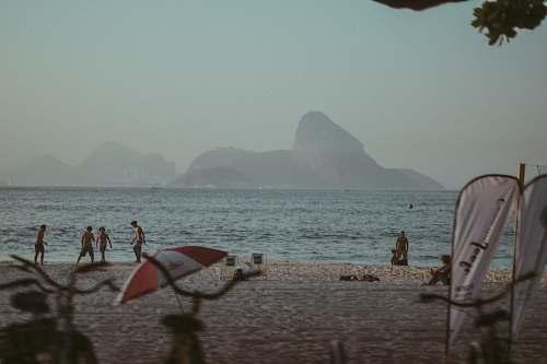coast people standing beside sea under gray sky beach