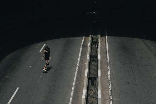 person high angle photo of woman riding on skateboard passing road grey