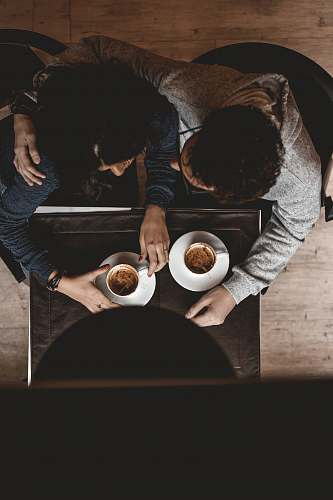 person man and woman sitting on floor while holding cups on table people