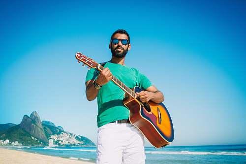 person man playing guitar near ocean during daytime people