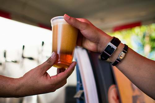 person person gives cup of beverage wristwatch