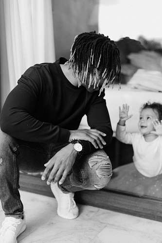 black-and-white shallow focus photo of man talking to baby person