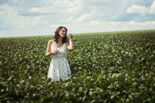 person woman standing in green leafed plant field during daytime people