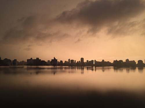 outdoors grayscale photography of city near body of water water