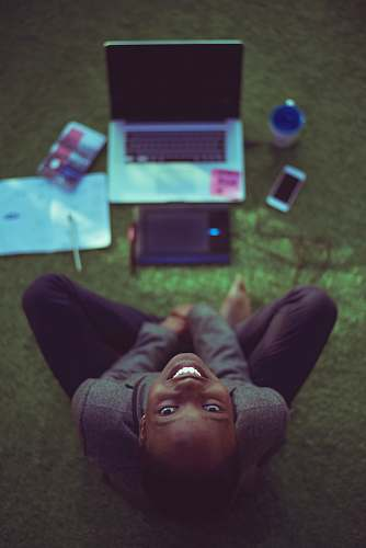 smile top view photo of woman sitting near MacBook Pro facing the camera covenant university