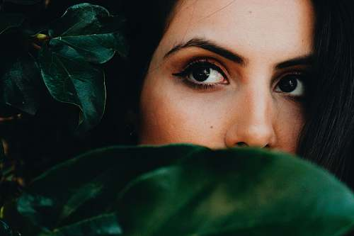 human half faced woman near green leaves person