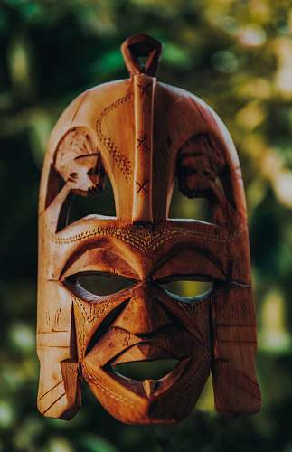human tilt shift lens photography of brown wooden mask person