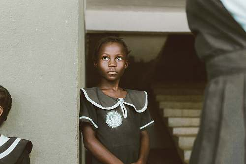 human girl leaning on white wall a liberia