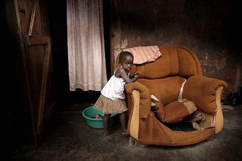 human girl standing near brown fabric sofa chair inside room people