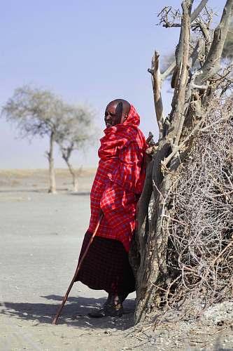 human man wearing red thawb robe holding cane people