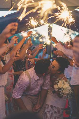 people newly wed kissing surrounded by people human