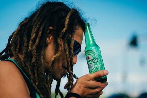 human person holding Heineken beer bottle bottle