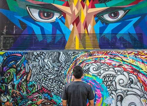 human photography of man seeing doddle wall art graffiti