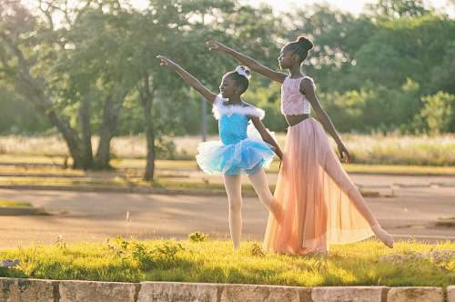 human two girls wearing blue and peach dresses dancing on green grass people