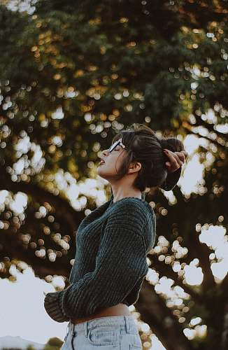 people woman wearing gray sweater near tree human