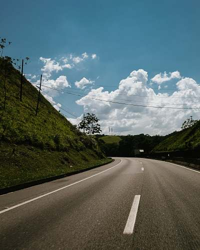asphalt green hill near road during daytime tarmac