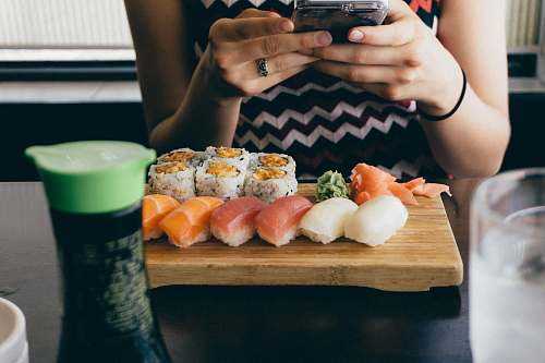 sushi person sitting in front of sushi dish on table human