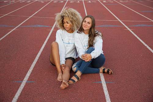 person photograph of two woman seating on track field people