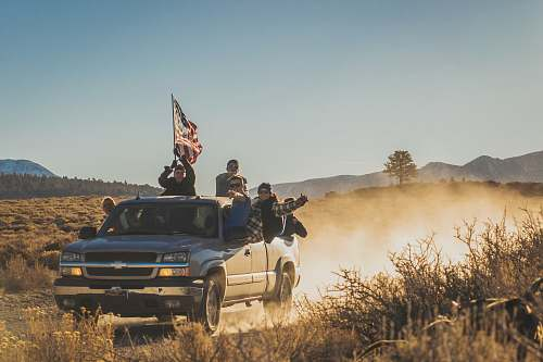 united states group of people riding silver Chevrolet extended cab road