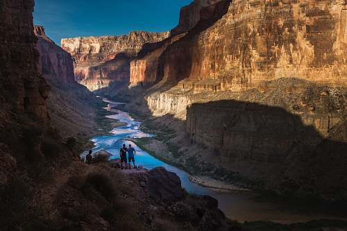 canyon two person standing on rocks facing body of water valley