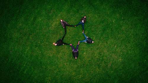 green five people laying on grass field making star sign field