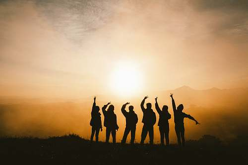 group silhouette photo of six persons on top of mountain friends