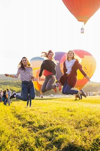 human three women jumping above green grass person