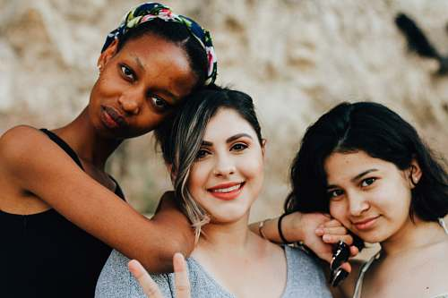 person three women posting for picture woman