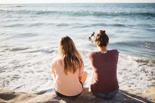 human two women sitting on cliff looking at the ocean beach
