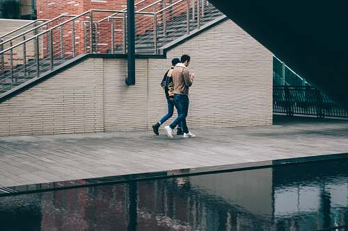 people two man walking beside stair and body of water at daytime human