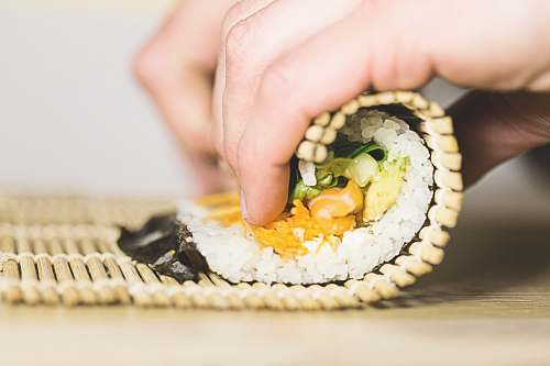 human person rolling sushi person